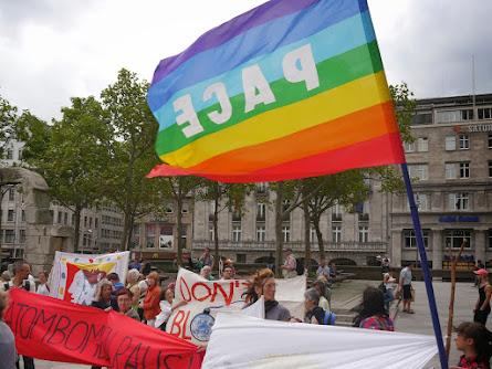Kundgebungsteilnehmerinnen mit Transparenten, »Atombomben raus!«, und Regenbogen-Friedensfahne »PACE«.