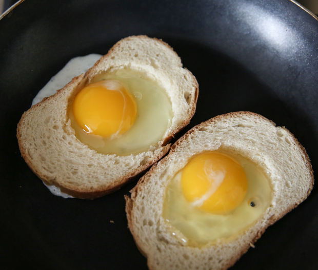 photo of the bread with the eggs in the hole cooking in a skillet