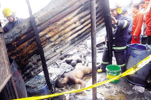 Anggota bomba mengalihkan sekeping zink yang menghempap mayat-mayat selepas sebuah pesawat ringan yang terhempas menyebabkan kebakaran di kawasan penempatan di daerah Paranaque, Manila, semalam.