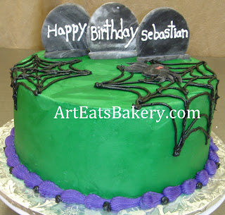 Green butter cream halloween birthday cake with black spider webs and tombstones