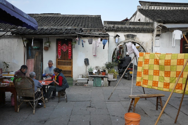 people playing cards outside of Chinese traditional style homes in Shaoxing, China