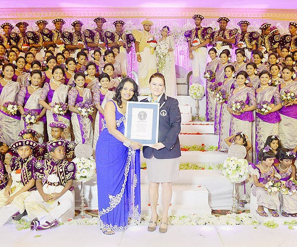 Sri Lankan couturier Champi Siriwardana (L) recieves her Guinness World Record award from Guinness World Record official Seyda Subasi Gemici (R) during the wedding of couple Nisansala and Nalin (background C) in Negombo, some 30kms north of Colombo, on November 8, 2013.
