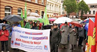 Demonstranten mit Regenschirmen und Transparent: »Faschismus ist keine Meinung sondern ein Verbrechen. Keine Toleranz für Nazis!«