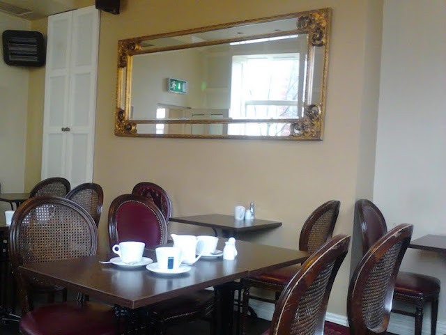dark-brown cafe tables and wicker work chairs, with white cups and plates, large gilt edged wall-hung mirror