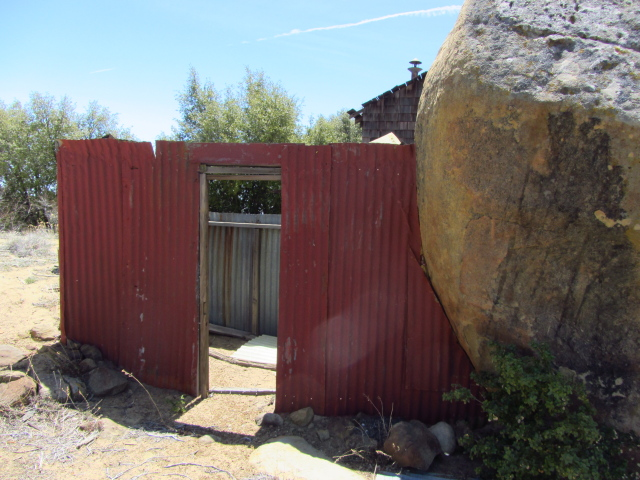 shed built with a boulder as one side