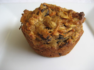Muffin with carrots, oats, and raisins on a white plate.