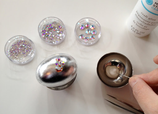 Place your egg in a small cup to hold it in place. Begin by gluing down a medium to large rhinestone in the center of your egg, using only as much glue as needed.