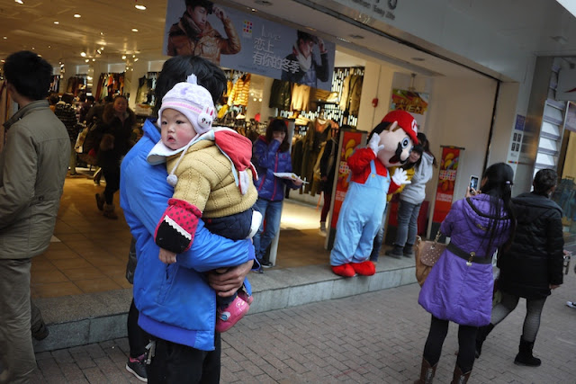baby away from a Mario mascot in Changsha, China