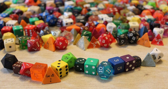a sea of gaming dice, with a rainbow of dice in the foreground