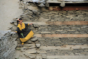 A Kalasha girl - A girl precariously perched on stone ledges. Some houses here can be easily accessed via stairs, while others can be reached only by scaling stone walls.