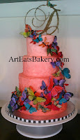 Coral ombre stucco butter cream with multi color feather butterflies and hand made monogram topper