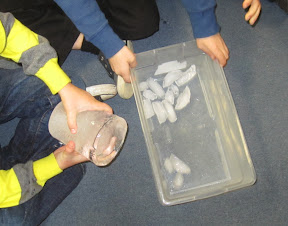 Children handle large and small ice blocks.