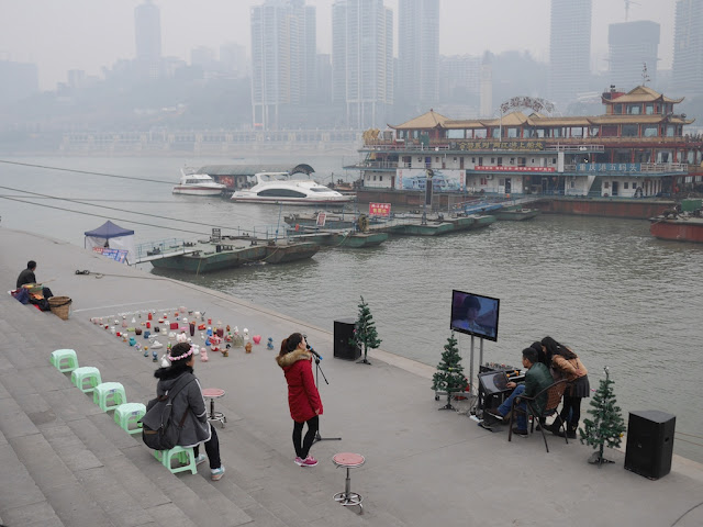 female college student singing karaoke outdoors at Chaotianmen Docks