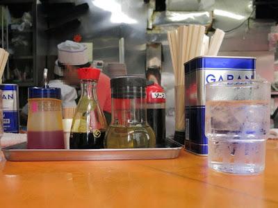 店内のカウンター上。醤油、酢、ラー油、コショウが置かれてる