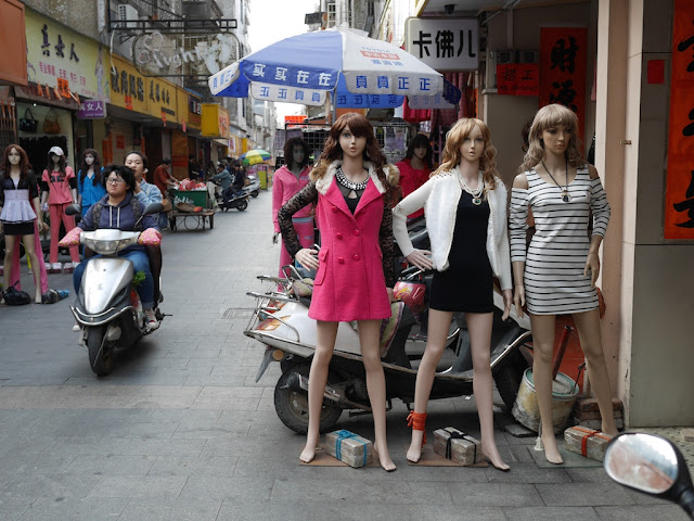 mannequins and two people on a motorbike in Yangjiang, China