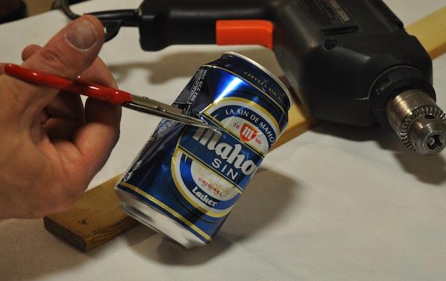 Contando con unas tijeras la chapa de la lata