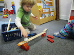 Young child builds a ramp with blocks and cove molding section, and rolls a ball down it.