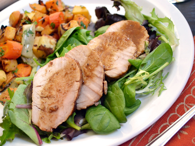 Four slices of Soy Dijon Pork Tenderloin on a. bed of greens with a side dish, plated