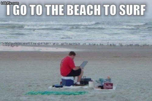 photo of a man at the beach, surfing the web