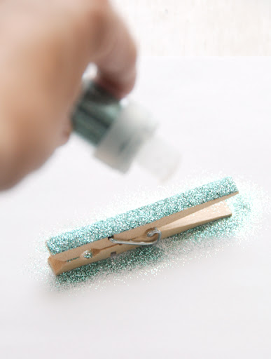 Glitter time! Lay your clothespin down on a piece of scrap paper, sticky side up (the scrap paper will come in handy for saving the leftover glitter).