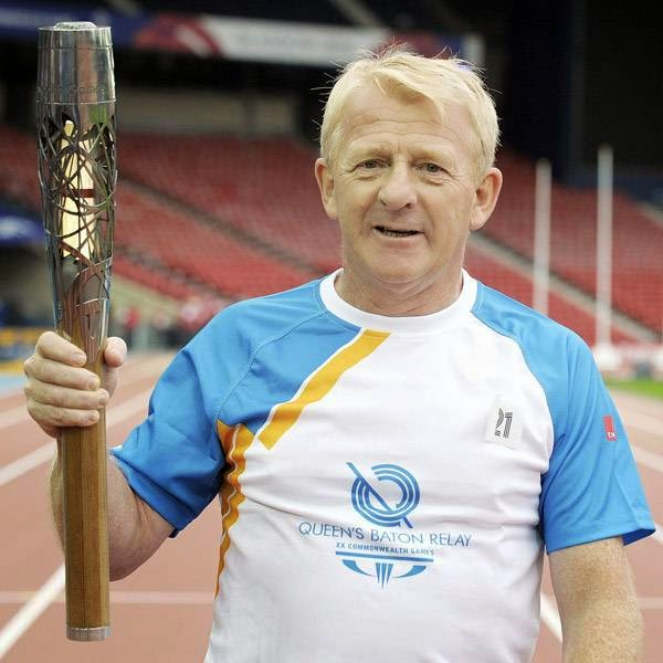 Gordon Strachan, manager of the Scottish national football team, carries the 2014 Commonwealth Games baton on the athletics track at Hampden Park Stadium in Glasgow on July 22, 2014