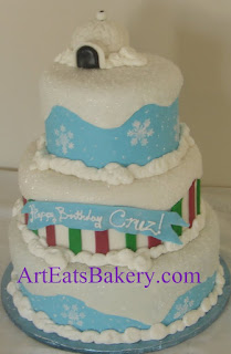 Three tier winter wonderland blue and white fondant birthday cake with snowflake and stripe desgn and edible igloo topper