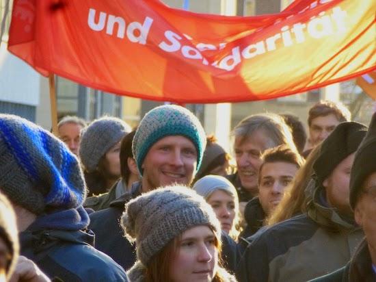 Demonstrierende mit Transparent: »...und Solidarität«.