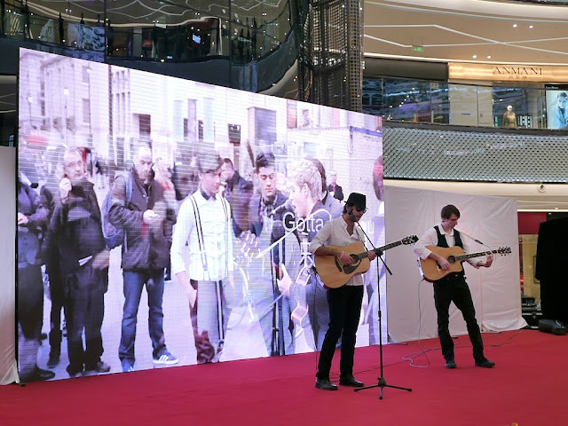 two men playing guitar in front of a video display