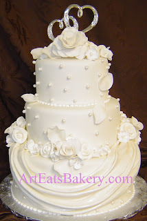 Three tier white fondant wedding cake with sugar pearls, flowers, drape design and silver hearts topper