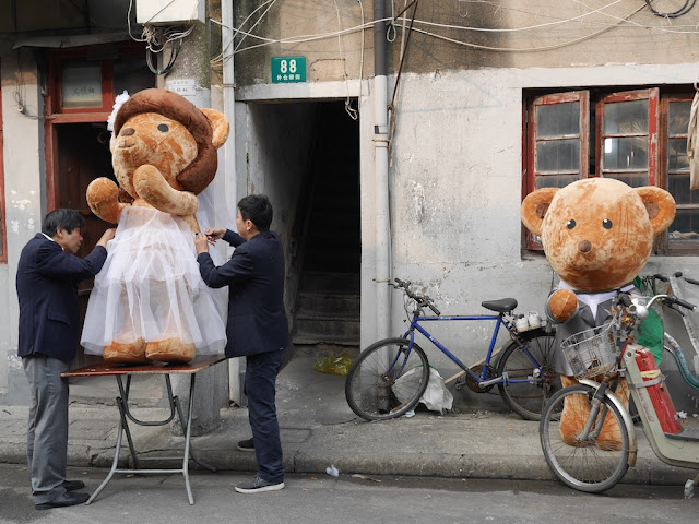 two men altering a wedding dress for a large stuffed bear with the groom stuffed bear nearby