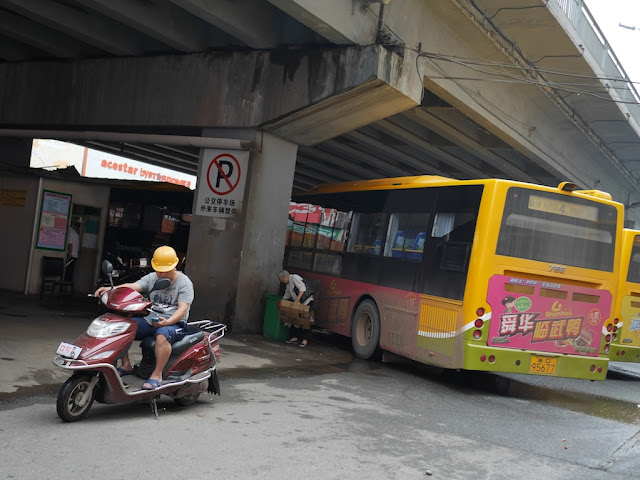 mototaxi driver sitting on a motorbike under a bridge