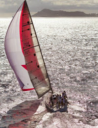 J/125 sailing under spinnaker to Transpac finish line off Hawaii