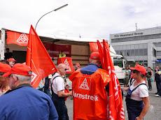 Kollegen mit roten IG Metall Fahnen, Mützen, Westen »Warnstreik«.