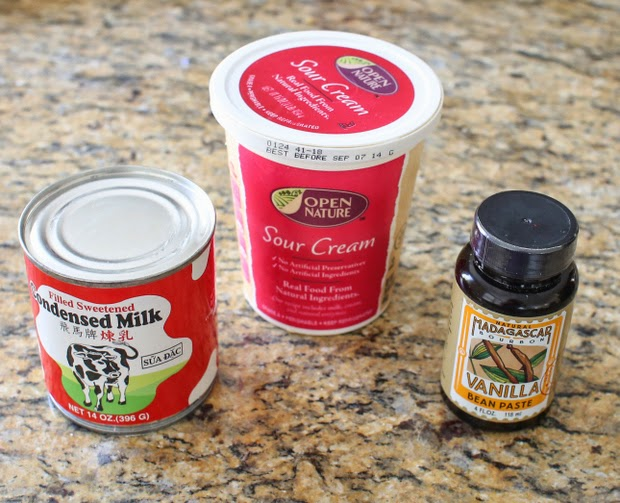 photo of a can of condensed milk, a carton of sour cream, and a container of vanilla paste