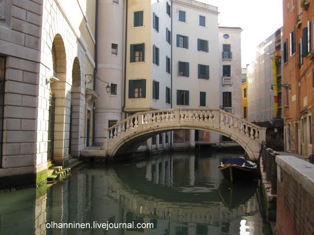Зеленая вода венецианского канала и белый мраморный мост
