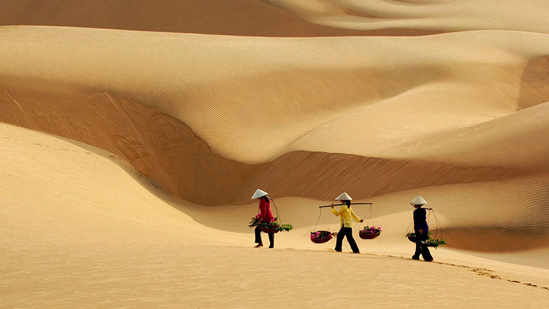 Ảnh phụ nữ gánh hàng đi qua bãi cát vàng