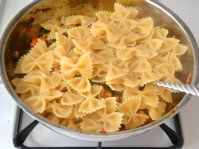 cooked pasta added to skillet with sauce
