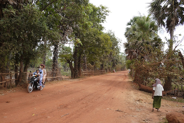 three people riding a motorbike on a dirt road