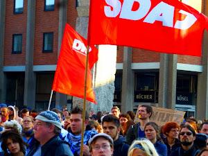 Demonstranten mit SDAJ- und DKP-Fahne.