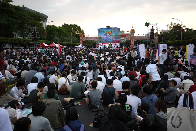 large crowd sitting on the ground with a colorful stage in the distance