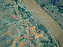 Another Madagascar village from the air, next to a wide river.