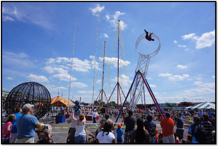 A daredevil goes upside down on a tall spinning trapeze high in the air.
