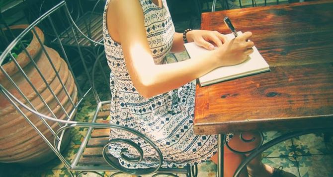 Ảnh cô gái đang ngồi viết sách, viết thư