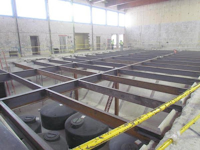 Steel over pool for middle school gym floor. Rainwater harvest tanks below