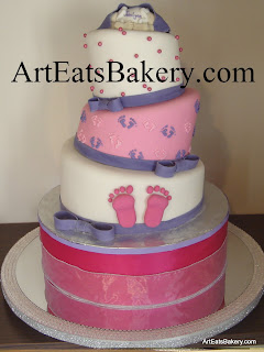Pink, white and purple topsy turvy or mad hatter baby shower cake design with feet, edible pearls, bows and baby behind topper