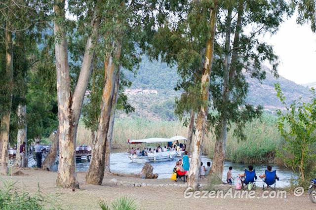 okaliptüs ağaçları gölgesinde azmak kıyısında oturanlar ve tekne ile azmak turu yapanlar, Kadın Azmağı Akyaka