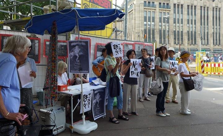 Infotisch, Demonstranten mit Plakaten.