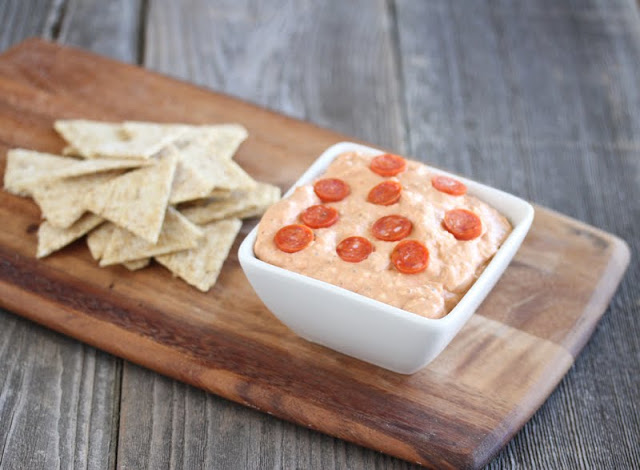 photo of a bowl of pizza dip on a board with crackers