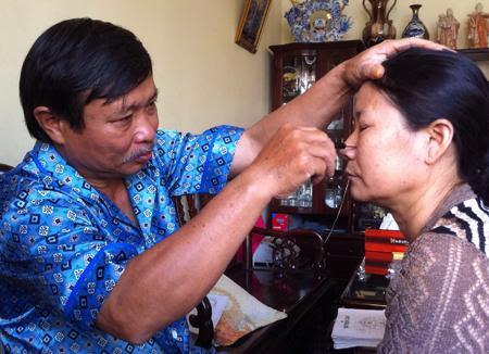 Ông Phan Văn Nga dùng dụng cụ bằng sắt day ấn huyệt đạo cho một người bệnh.