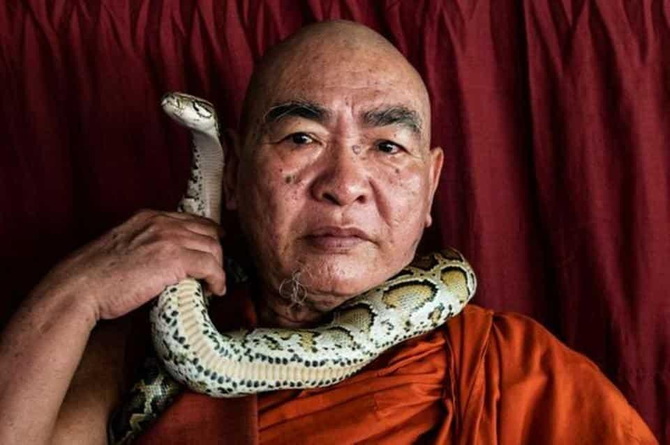 Buddhist monk Wilatha poses with a rescued Burmese python at his monastery that has turned into a snake sanctuary on the outskirts of Yangon, Myanmar.